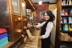 Stående för sidosikt av fördelande kaffebönor för kvinnlig affärsbiträde in i pappers- påse på lagret Royaltyfri Foto
