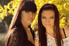 Stående för två brunettkvinnor utomhus. Arkivbild