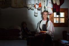 Stående för ung kvinna inom traditionellt hem med den rumänska traditionella dräkten arkivfoto