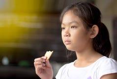 Stående flicka som äter en kaka, mat, hållande kaka för flicka Royaltyfri Bild
