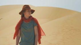 Stående: Flickahandelsresande i öknen på sanden Bära en hatt och en röd halsduk Undersöker forntida terräng som söker stock video