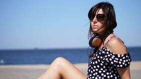 Stående, härlig brunett, kvinna i solexponeringsglas och hörlurar som sitter på stranden, mot havet vindvågor stock video