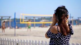 Stående härlig flicka i solexponeringsglas som bär stor svart hörlurar som lyssnar till musik från smartphonen, på stranden, på arkivfilmer