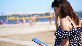 Stående härlig flicka i solexponeringsglasarbete på en minnestavla, på stranden, på en varm sommardag, mot en bakgrund av stock video
