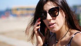 Stående härlig flicka, kvinna i solexponeringsglas som talar på en mobiltelefon på stranden på en varm sommardag, arkivfilmer