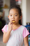 Stående hållande kaka för flicka, flicka som äter en kaka, mat Royaltyfria Foton