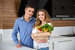 Stående hållande pappers- påse för lyckliga par med nya grönsaker Royaltyfri Bild