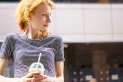 Stående i profil av den unga kvinnan med drinken på gatan Royaltyfria Bilder