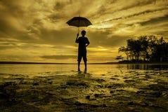 Stående innehav för pojke ett paraply under solnedgångsoluppgång Royaltyfri Bild