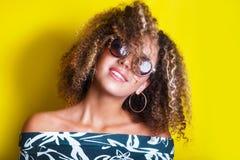 Stående inomhus av en ung afro amerikansk kvinna i solglasögon Gul bakgrund livsstil tillfälliga kläder royaltyfria bilder