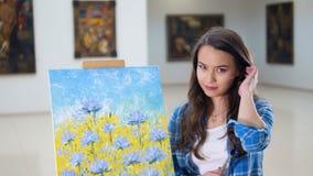Stående Konstnär som ler att stå nära en bild av blommor lager videofilmer