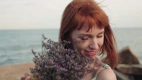 Stående långsam rörelse Den härliga sexiga flickan poserar positivt med blommor på havet arkivfilmer