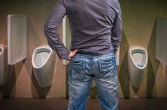 Stående man som peeing till en pissoar i toalett fotografering för bildbyråer