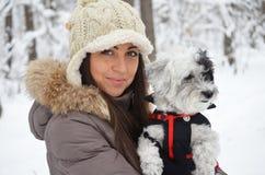Stående på den härliga kvinnan som kramar hennes hund i vinterskogen Fotografering för Bildbyråer