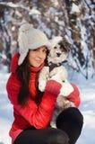 Stående på den härliga kvinnan som kramar hennes hund i vinterskogen Arkivfoto