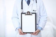 Stående raksträcka för okänd manlig doktor medan hållande medicinsk skrivplatta med tom vitbok care hälsomedicinen Fotografering för Bildbyråer