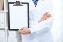 Stående raksträcka för okänd manlig doktor medan hållande medicinsk skrivplatta med tom vitbok care hälsomedicinen royaltyfria foton