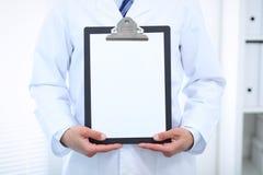Stående raksträcka för okänd manlig doktor medan hållande medicinsk skrivplatta med tom vitbok care hälsomedicinen Arkivbild