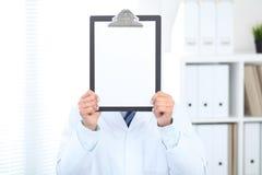 Stående raksträcka för okänd manlig doktor medan hållande medicinsk skrivplatta med tom vitbok i stället för hans framsida Royaltyfri Bild