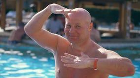 Stående rolig skallig medelålders man, med en naken torso, något roliga allsånger, danser, vid pölen på semester, in lager videofilmer