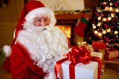 Stående Santa Claus med gåvan för dig Arkivbilder
