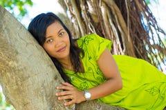 Stående som är nära upp av den unga härliga asiatiska flickan som lägger på banyanträdet som ser kameran Royaltyfri Fotografi