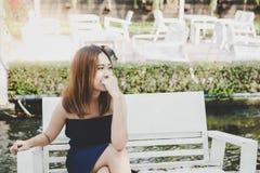 Stående som charmar den härliga unga kvinnan: Den attraktiva asiatiska flickan ser något som gör hennes skratta fotografering för bildbyråer