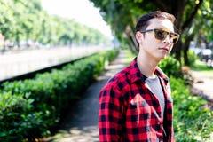 Stående som charmar den stiliga unga mannen Attraktiv grabbklädersungla fotografering för bildbyråer