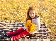Stående som ler barnet med gula lönnblad som sitter på plädet i solig höst arkivfoton