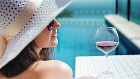 Stående som ler den nätta kvinnan i diskett hatt och solglasögon som tycker om att solbada med bägaren av vin stock video