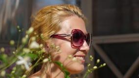 Stående som ler kvinnan i solglasögon som tycker om solig dag på sommarträdgården lager videofilmer