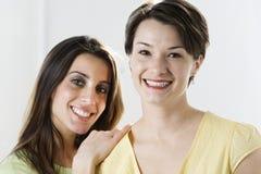 stående som ler två kvinnor Royaltyfria Foton