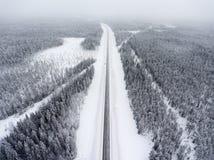 Stående vägren för liten enkel bil i vintrig väg på häftiga snöstormen, flyg- sikt på den raka nordliga rutten Karelia Ryssland royaltyfria foton