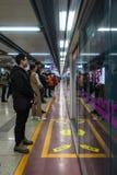 Stående väntande på gångtunnel för kinesiskt folk bak Glass Reflecti royaltyfri fotografi