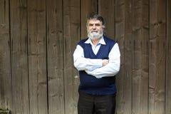 Stående yttersida för äldre man på trä arkivfoton