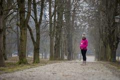 Stående yttersida för gravid kvinna i en parkera Arkivfoton