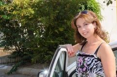 Stående yttersida för kvinna hennes bil och le Royaltyfri Foto