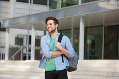 Stående yttersida för lycklig manlig högskolestudent med påsen Arkivfoto