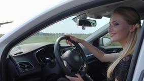 Ståendeavtodamen sitter bak den moderna nya bilen för hjulet som ler och ser kameran stock video