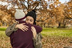 Ståendebarnet kopplar ihop att krama i en höstbakgrund tillbaka sikt Royaltyfria Foton