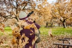Ståendebarnet kopplar ihop att krama i ett regn av sidor i höst bac Royaltyfri Fotografi