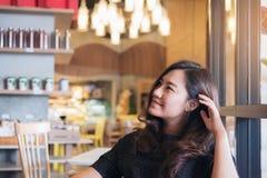 Ståendebild av en härlig asiatisk kvinna för smiley med mening bra av sitta och av att koppla av i modernt kafé arkivbild