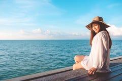 Ståendebild av en lycklig härlig asiatisk kvinna på vitt klänningsammanträde på träbalkong vid havet med klar blå himmel royaltyfri fotografi