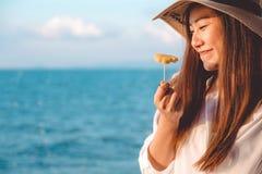 Ståendebilden av en lycklig härlig asiatisk kvinna tycker om att äta ananas vid havet med klar blå himmel arkivbild