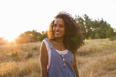 Ståendedet fria av en härlig ung afro amerikansk kvinnasmili arkivfoton