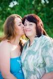 Ståendedottern är kyssande hennes moder på kinden i den soliga dagen för sommar royaltyfri foto