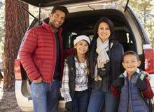 Ståendefamilj som utomhus tillbaka står på det öppet av bilen royaltyfri bild