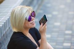 Ståendeflicka som talar utomhus på telefonen royaltyfri bild