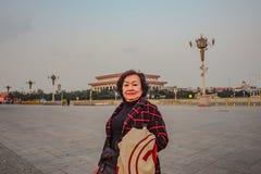 Ståendefoto av den höga asiatiska kvinnahandelsresanden på den Tiananmen fyrkanten i den beijing staden royaltyfri bild