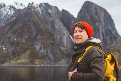 Ståendehandelsresandeman med en gul ryggsäck som bär en röd hatt på kusten på bakgrunden av berget och sjön royaltyfria bilder
